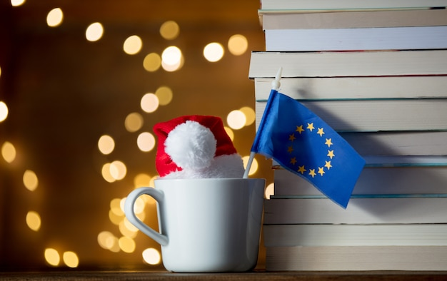 Xícara branca e chapéu de natal com a bandeira da união da europa