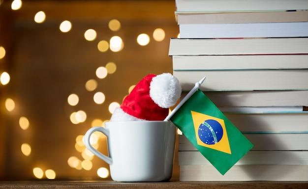 Xícara branca e chapéu de natal com bandeira do brasil perto de livros