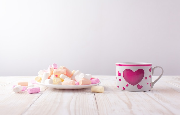 Xícara com a foto de um coração e um pires com marshmallows em uma mesa de madeira branca