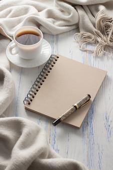 Xícara com café, bloco de notas em cima da mesa de madeira branca. conceito de primavera
