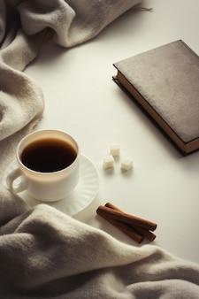Xícara com café, cachecol, livro na superfície branca