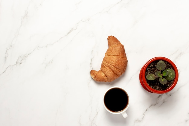 Xícara com café, croissant e planta de casa em uma mesa de mármore. conceito de pequeno-almoço. camada plana, vista superior