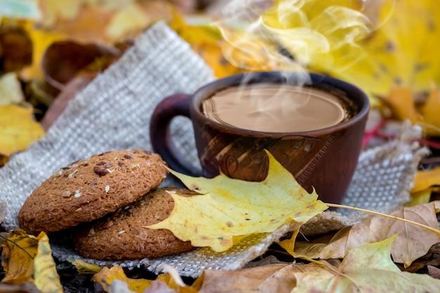 Xícara com café e biscoitos no parque outono entre folhas amarelas