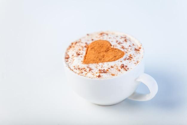 Xícara com café e formato do coração de cacau