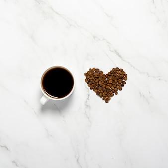 Xícara com café e uma forma de coração feita de grãos de café em uma mesa de mármore. quadrado. conceito de café da manhã, café da noite, insônia, amor pelo café. vista plana, vista superior