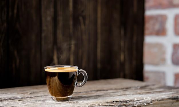 Xícara com café expresso disposto sobre uma mesa de madeira escura. close up, foco seletivo, espaço de cópia