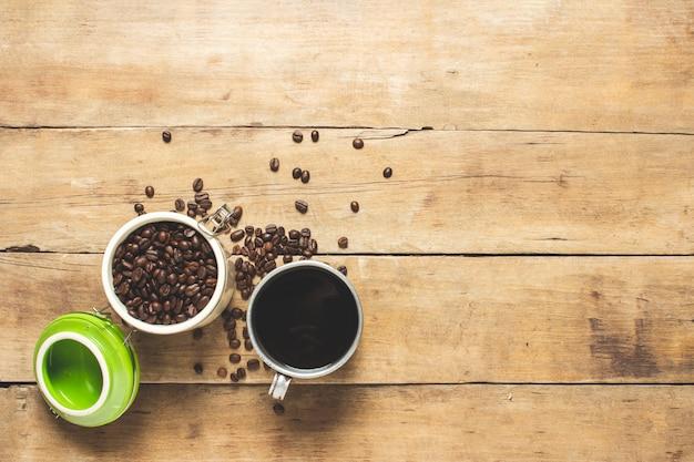 Xícara com café fresco e uma lata com grãos de café, grãos de café estão espalhados sobre uma mesa de madeira.