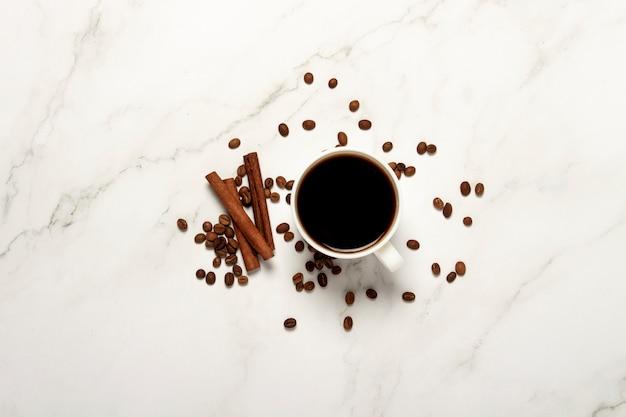 Xícara com café, grãos de café e paus de canela em um fundo de mármore. vista plana, vista superior