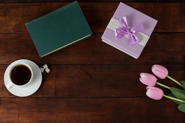Xícara com café, livro, presente, tulipas em uma superfície de madeira escura