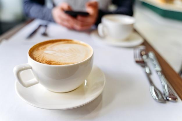 Xícara com café na mesa de uma cafeteria. homem usando um telefone