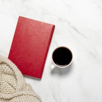 Xícara com café ou chá, um cachecol de malha e um livro sobre uma mesa de mármore. conceito de café da manhã, educação, conhecimento, livros de leitura, lazer de inverno. vista plana, vista superior