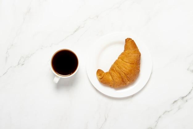 Xícara com café preto e croissant em uma mesa de mármore