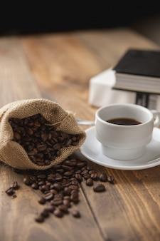 Xícara com café quente e alguns livros para ler