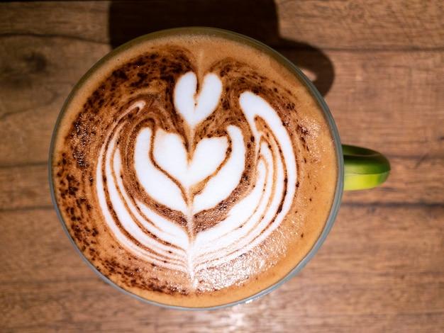 Xícara com cappuccino com espuma latte art de forma de coração na mesa de madeira preta na casa de café. uma bebida de cafeína fumegante na mesa do café.