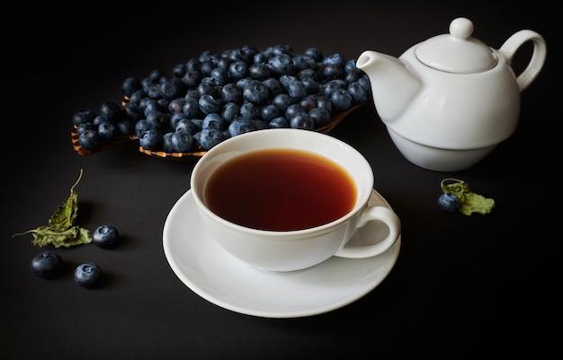 Xícara com chá, bule, mirtilo e folhas secas de mellisa em fundo escuro