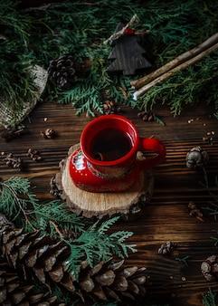 Xícara com chá com galhos de uma árvore de natal e cones em uma madeira velha