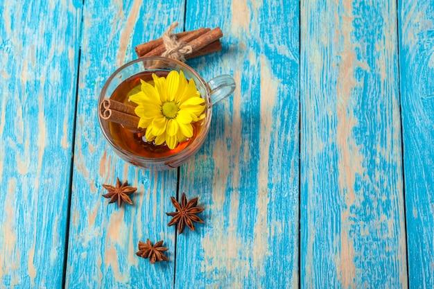 Xícara com chá de canela quente aromático na mesa de madeira