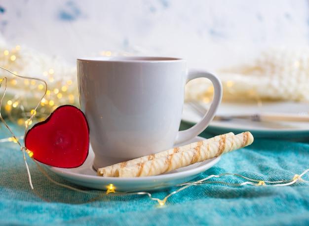 Xícara com chá sobre um fundo claro e um presente para o dia dos namorados. café da manhã romântico do dia das mães.