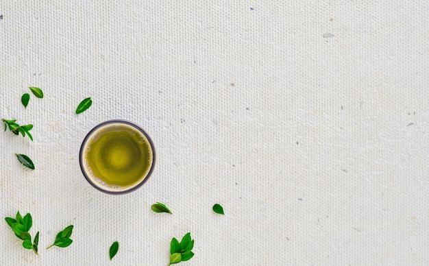 Xícara com chá verde, ao lado das folhas verdes, vista superior com espaço de cópia. conceito de design, minimalismo