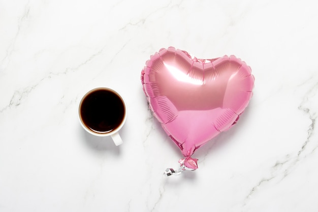 Xícara com coração de café e balão de ar em uma mesa de mármore