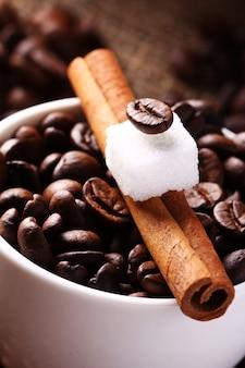Xícara com grãos de café e canela em pau
