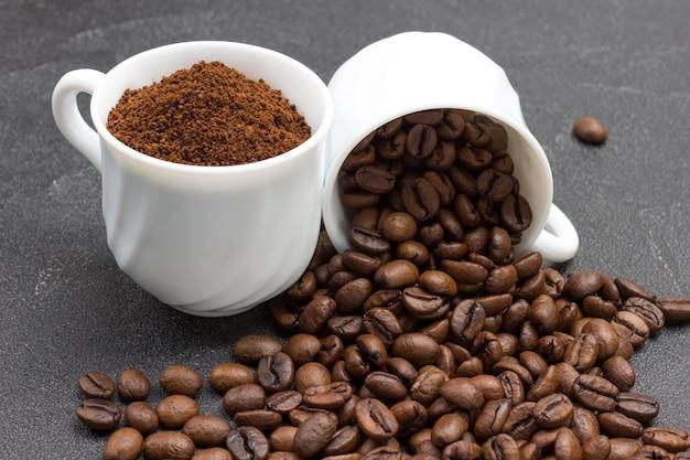 Xícara com grãos de café moídos. xícara com grãos de café torrados. fundo preto.