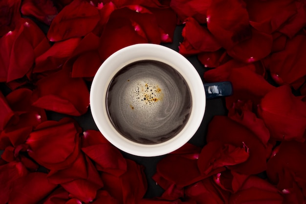 Xícara com vista superior de café com pétalas de rosa