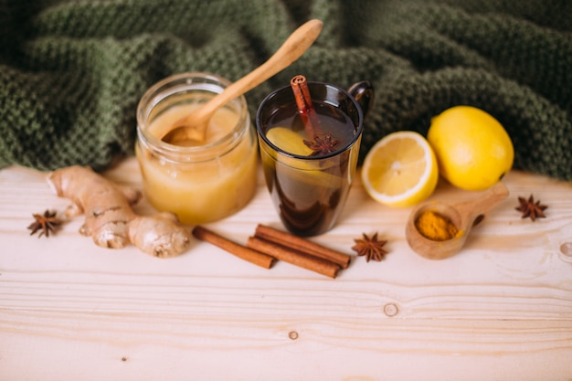 Xícara de água morna com limão, mel, gengibre, canela e anis.
