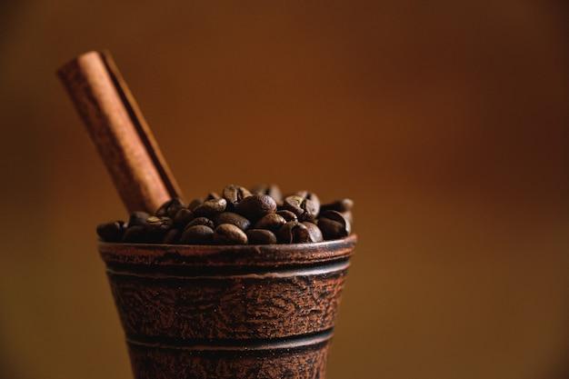 Xícara de barro com grãos de café e canela em uma mesa de madeira.