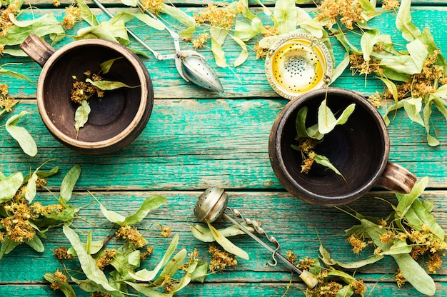Xícara de barro e folhagem fresca e inflorescências de tília. medicamento herbário e homeopatia. plantas curativas.