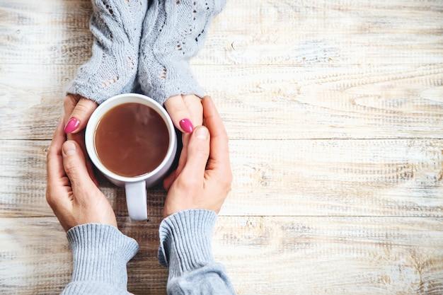 Xícara de bebida no café da manhã nas mãos dos amantes.
