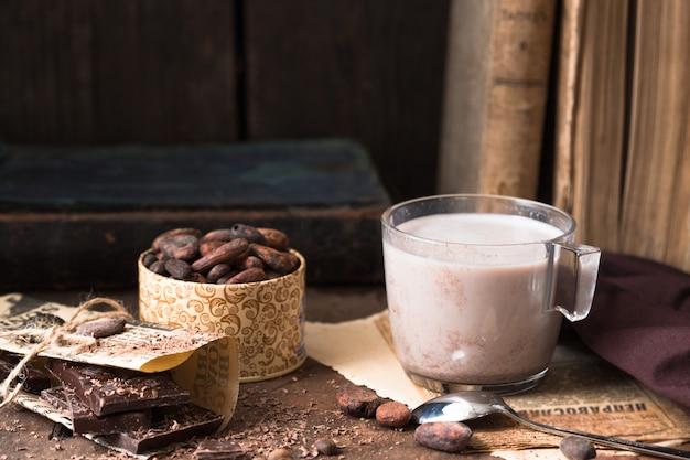 Xícara de cacau aromático na mesa antiga com grãos de cacau