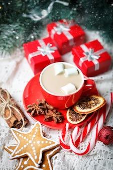 Xícara de cacau, biscoitos, presentes e galhos de pinheiro em uma mesa de madeira branca