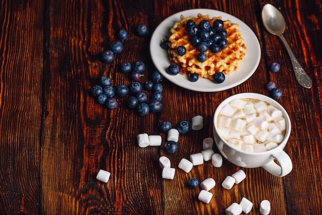 Xícara de cacau com marshmallow com waffles no prato com mirtilo fresco. colher e algumas frutas e marshmallows espalhados na mesa de madeira.