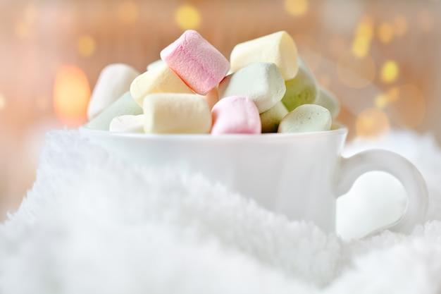 Xícara de cacau e marshmallows sobre um fundo claro
