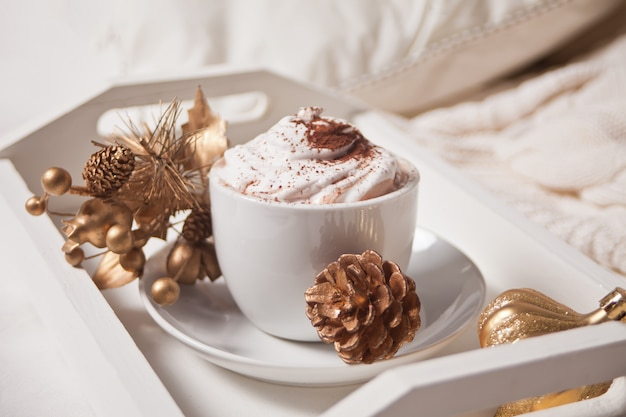 Xícara de cacau na bandeja branca na cama de manhã cedo de inverno
