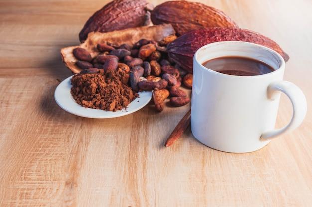 Xícara de cacau quente com cacau em pó e grãos de cacau no fundo de madeira