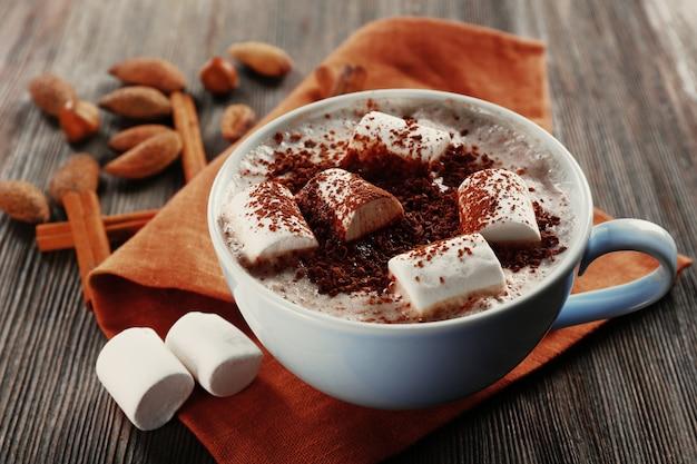Xícara de cacau quente com marshmallow, canela e nozes em guardanapo de algodão marrom, close-up