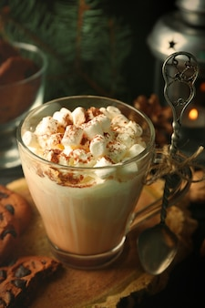 Xícara de cacau quente com marshmallow e biscoitos na mesa preta