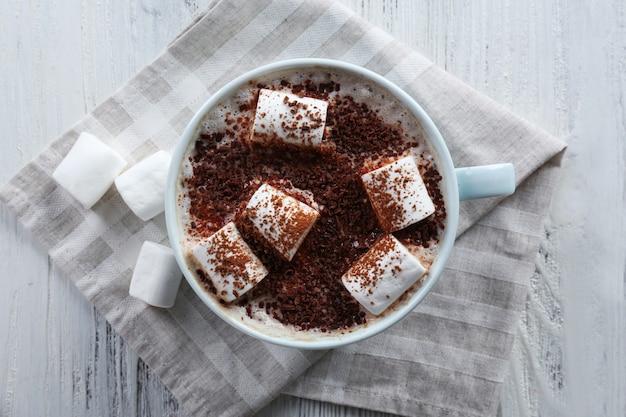 Xícara de cacau quente com marshmallow no guardanapo de algodão