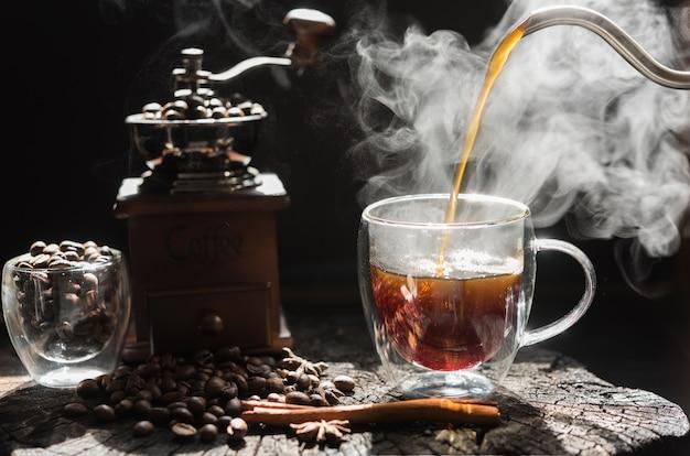 Xícara de café a vapor com moedor, cerveja, chaleira e copo de vidro em fundo escuro de mesa de madeira de grunge