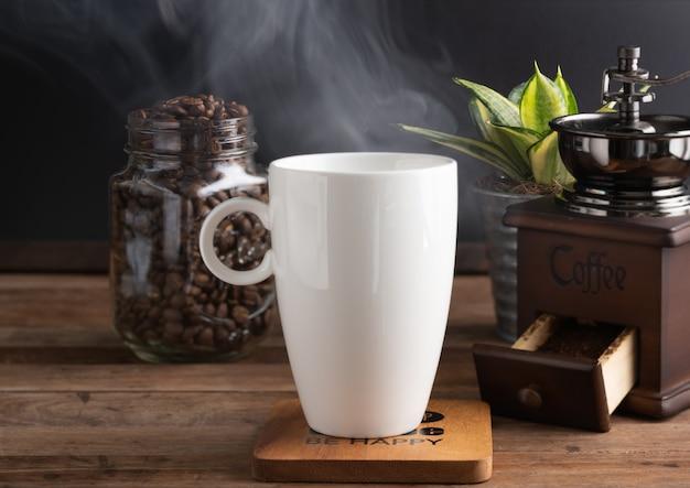 Xícara de café a vapor com moedor, feijão assado e vaso de flores sobre fundo de madeira na luz solar da manhã