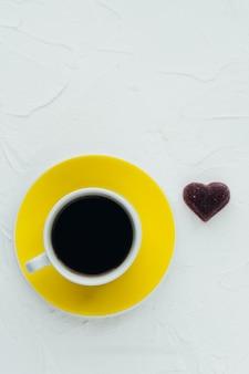 Xícara de café amarela e coração em um fundo branco. minimalismo. copie o espaço. foto vertical