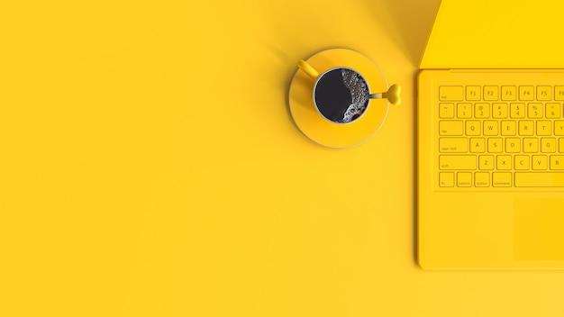 Xícara de café amarelo ao lado de laptop na mesa de trabalho vista de cima e espaço de cópia