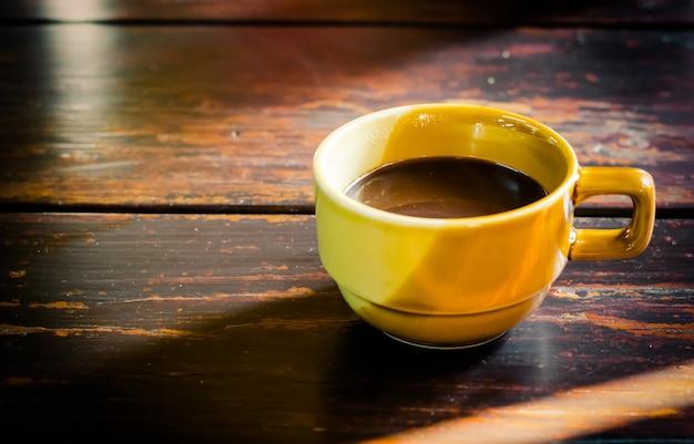 Xícara de café amarelo na velha mesa de madeira entre a luz do sol