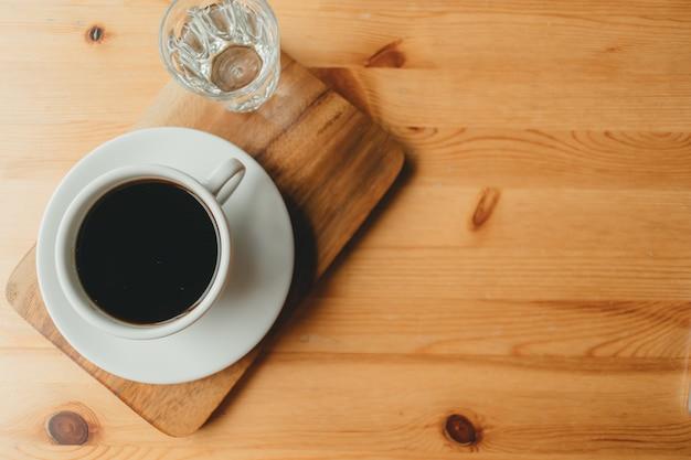 Xícara de café americano quente na mesa de madeira.