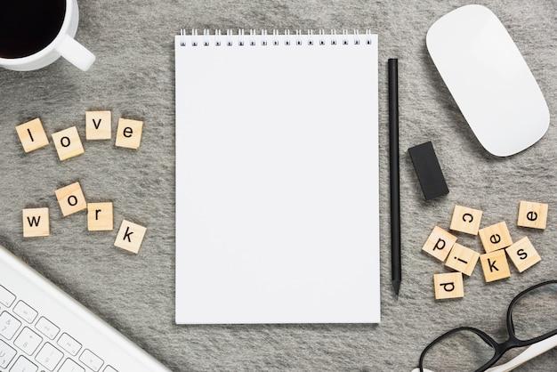 Xícara de café; amo blocos de trabalho; teclado; rato; bloco de notas em espiral; lápis e borracha em pano de fundo cinzento