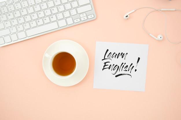 Xícara de café ao lado para aprender mock-up inglês nota auto-adesiva