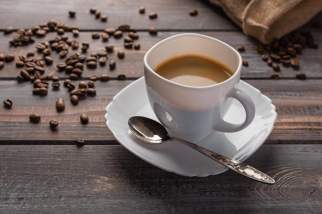 Xícara de café aromático com uma colher em um guardanapo de linho, grãos de café e saco