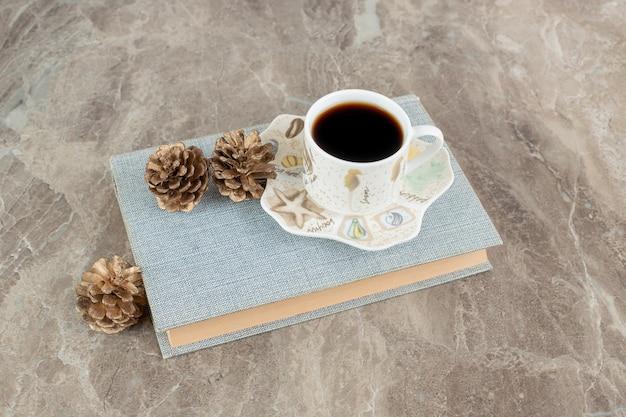 Xícara de café aromático em cima de livro com pinhas
